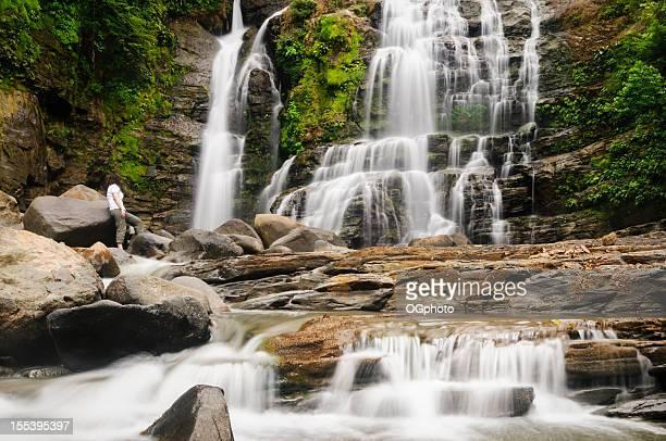 Woman admiring a beautiful waterfall