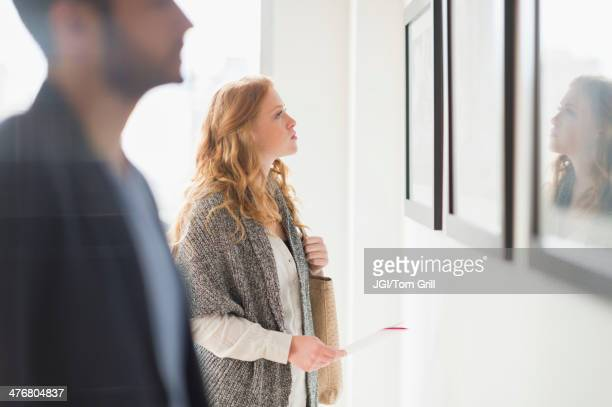 woman admiring art in gallery - kunst stock-fotos und bilder