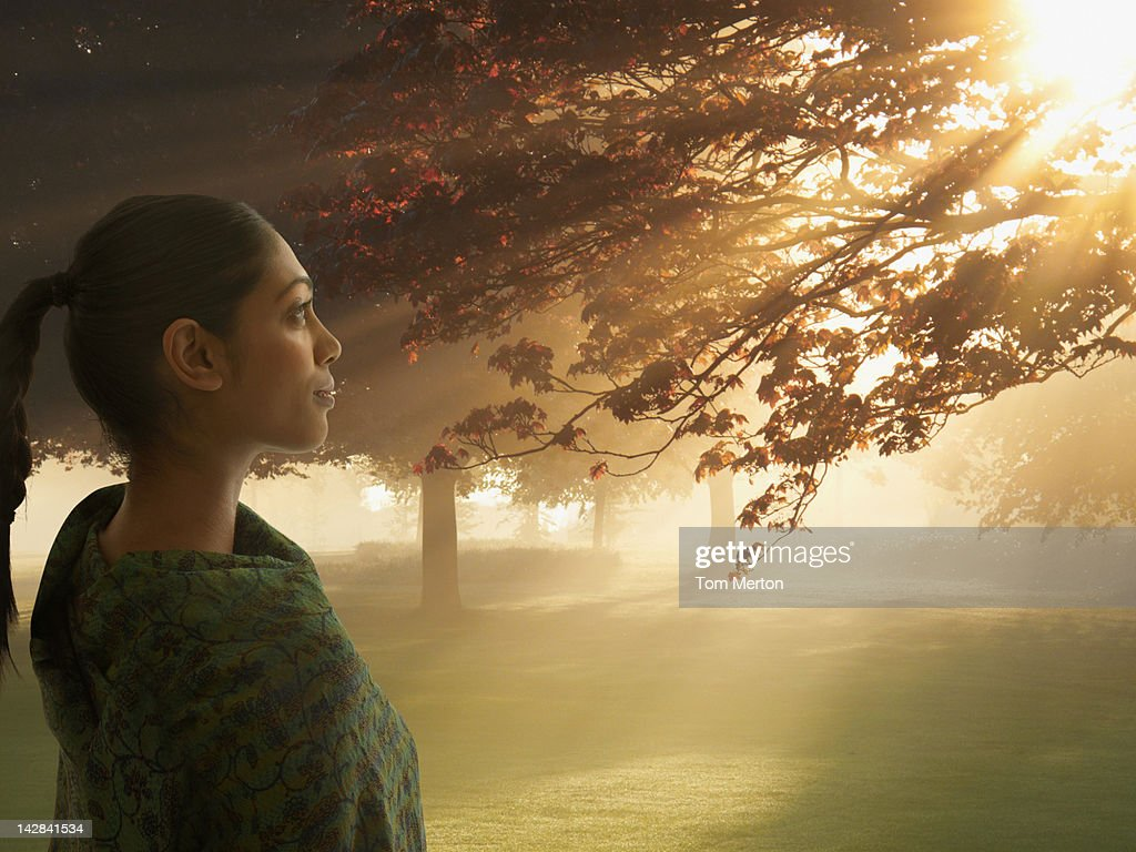 Woman admiring autumn leaves in field : Stock Photo