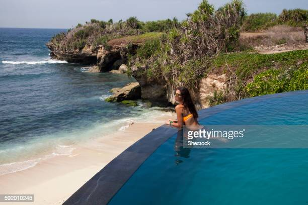 Woman admiring beach view from swimming pool