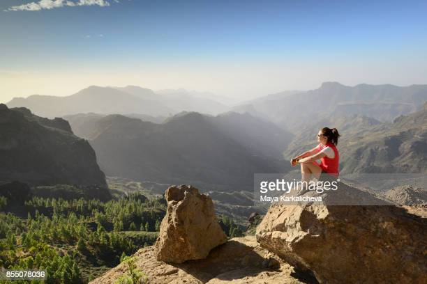 woman admiring beautiful volcanic mountain view of canary islands, gran canaria, roque nublo - one young woman only stock pictures, royalty-free photos & images