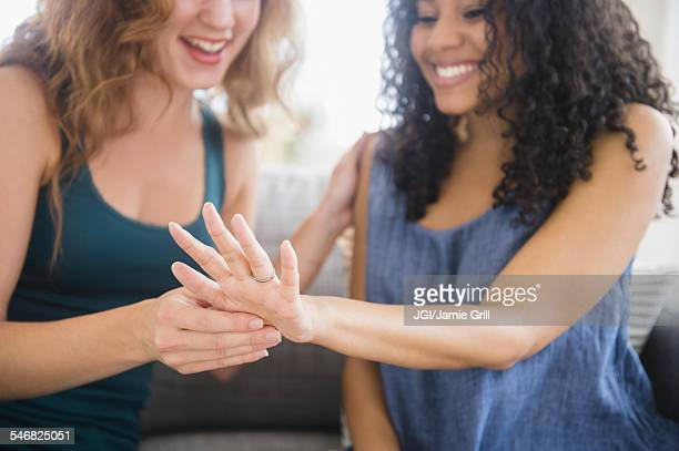 woman admiring engagement ring of friend - black women engagement rings stock pictures, royalty-free photos & images