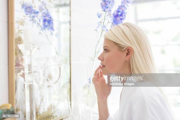 Woman admiring herself in bathroom mirror