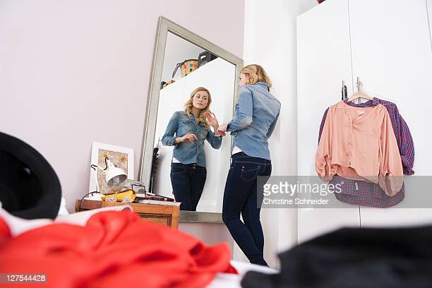 woman admiring herself in mirror - girl in mirror stock-fotos und bilder
