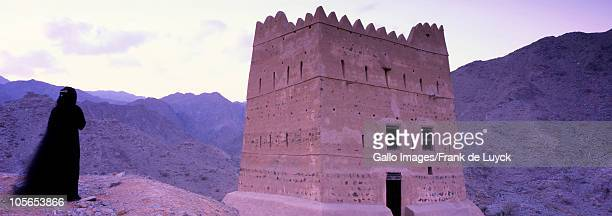 Woman admiring remains of Summer Palace of Sheikh Abdullah bin Hamdan al-Sharqi, Wadi Hayl, Fujairah, United Arab Emirates.