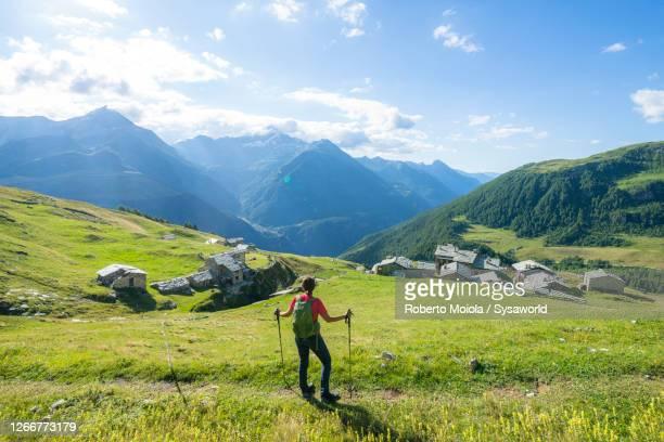 woman admiring the alpine village, toiana, valtellina, italy - gente serena foto e immagini stock