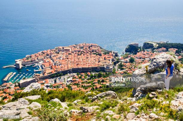 Woman admiring the city of Dubrovnik, Croatia from a hillside