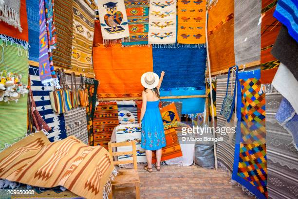 woman admiring the handmade rugs in oaxaca valley, mexico - craft product stock pictures, royalty-free photos & images