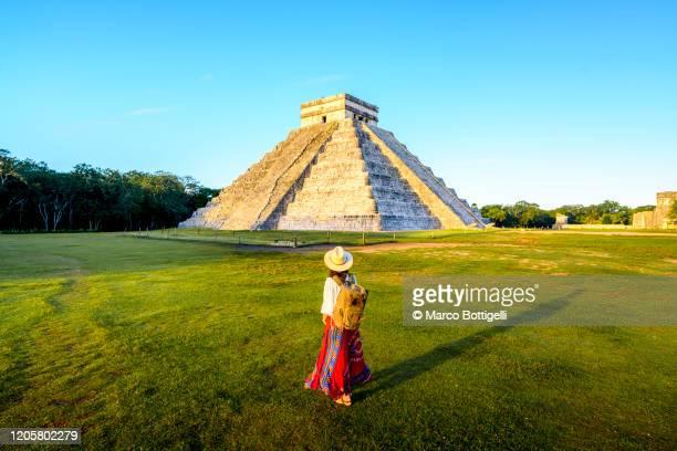 woman admiring the temple of kukulcan (el castillo) in chichen itza, yucatan, mexico - méxico fotografías e imágenes de stock