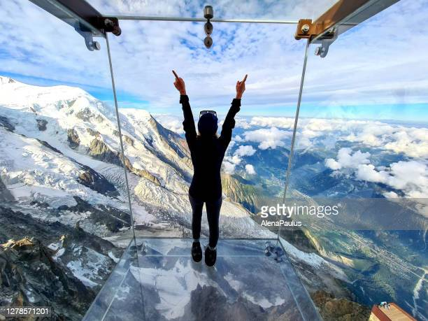 woman admiring the view from the glass box, the step into the void - aiguille du midi skywalk - elevated walkway stock pictures, royalty-free photos & images