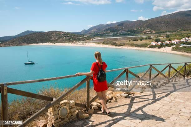 mujer admirando la vista de torre di chia, sardinia - países del golfo fotografías e imágenes de stock