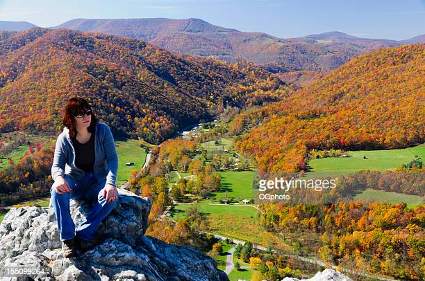 woman admiring the view of colorful autumn woods - ogphoto stock photos and pictures