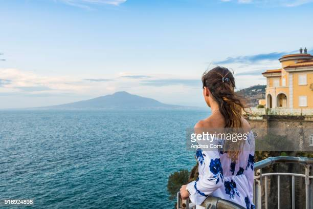 woman admiring the view of the gulf of naples. vesuvius in the background - mediterranean culture stock pictures, royalty-free photos & images