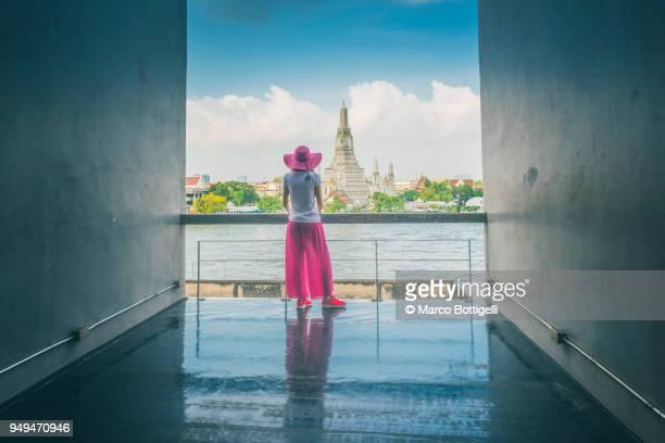 Woman admiring the Wat Arun (Temple of Dawn) and Chao Phraya River, Bangkok, Thailand.