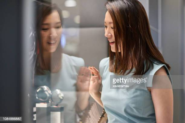 woman admiring watches through window display - fashion hong kong stock photos and pictures