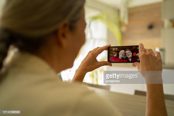 woman adult daughter connected with her senior parents through mobile phone video call during coronavirus crisis - illness prevention stock pictures, royalty-free photos & images