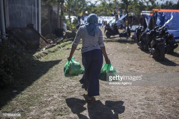 A woman affected by earthquake carries donations and charities distributed by volunteers at a temporary shelter in Lombok Indonesia on August 13 2018...
