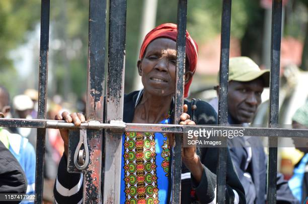 A woman affected by the post poll violence looks on through an iron gate after hearing of the main case to seek compensation was suspended pending...