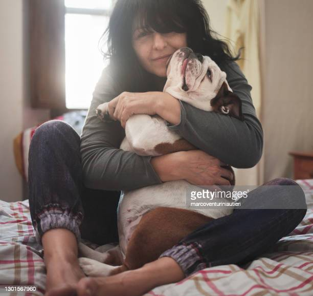 woman affectionately hugs her english bulldog in the bedroom - marcoventuriniautieri stock pictures, royalty-free photos & images