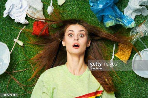 a woman after a party lies in a mountain of debris and plastic pollution - cleaning after party stock pictures, royalty-free photos & images