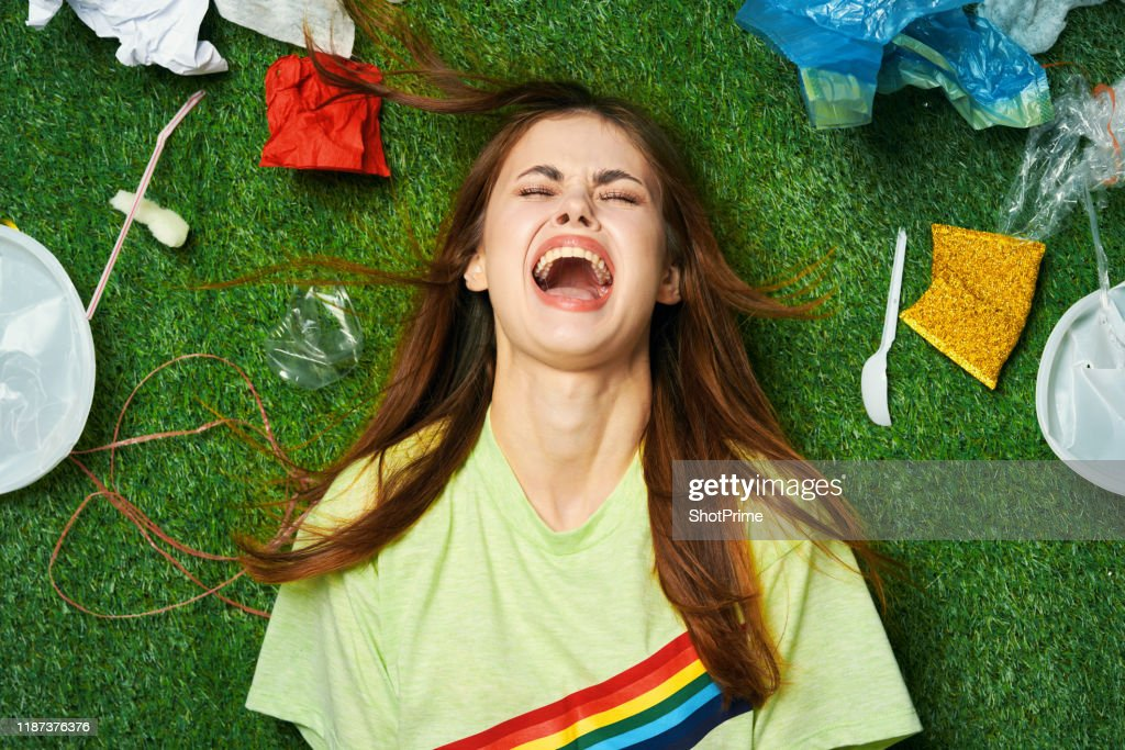 A woman after a party lies in a mountain of debris and plastic pollution : Stock Photo