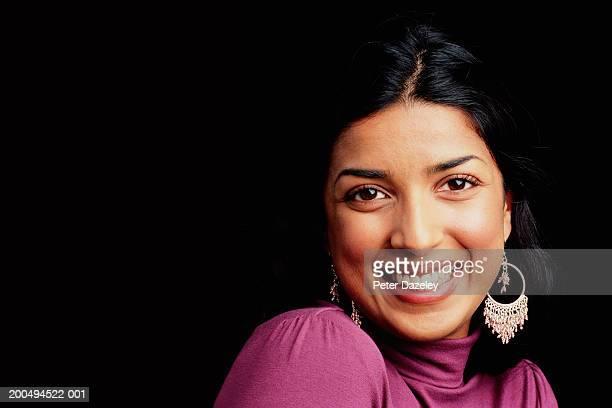 Woman against black background, smiling, portrait