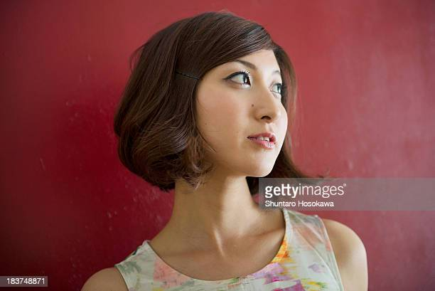 woman against red wall looking into distance - チャタム ストックフォトと画像