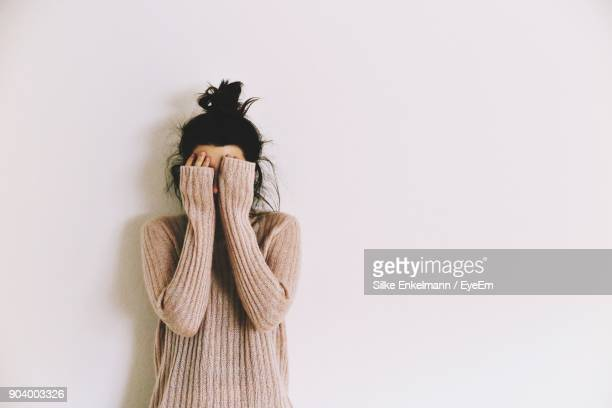 woman against wall - sweater stock pictures, royalty-free photos & images