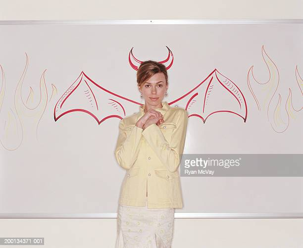 woman against whiteboard illustrated with devil wings and flames - devil costume stock photos and pictures