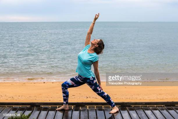 woman aged 50 years and older in standing yoga pose. - 55 59 years stock pictures, royalty-free photos & images