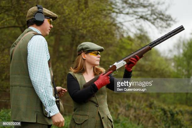 A woman aiming a rifle during at clay pigeon shoot
