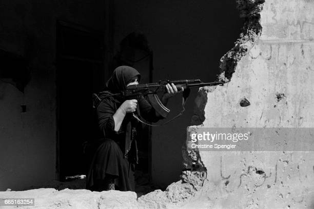 A woman aims an AK47 rifle over a crumbling wall in West Beirut during the Lebanese Civil War
