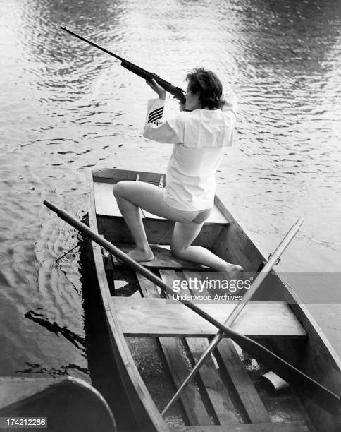 A woman aims and shoots a rifle while kneeling in a rowboat United States 1952