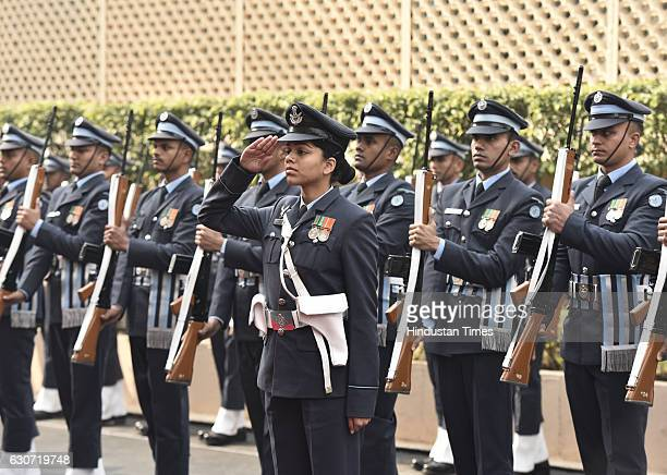 A woman Air Force officer salutes New Air Chief Marshal Birender Singh Dhanoa during his guard of honour ceremony at Air Force Headquarters before...