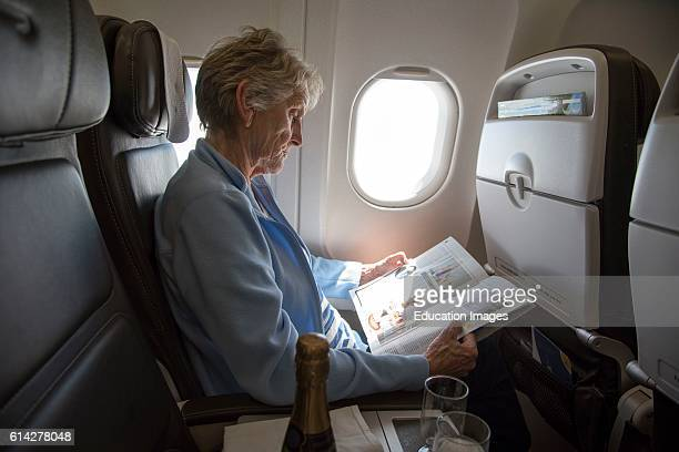 Woman Airline Passenger Onboard a Commercial Jet An Elderly Lady Passenger Seated By An Aircraft Window Reading a Magazine