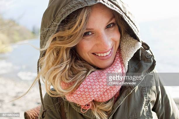Woman all wrapped up on windy beach