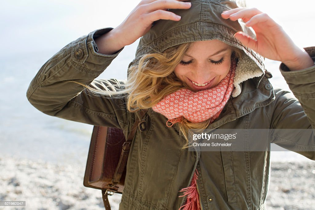Woman all wrapped up on windy beach : Stock Photo
