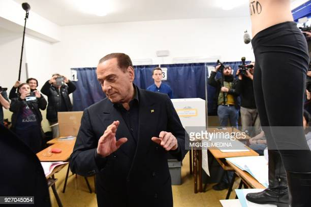TOPSHOT A woman alleged Femen activist jumps on a table in front of Silvio Berlusconi leader of rightwing party Forza Italia to protest topless with...