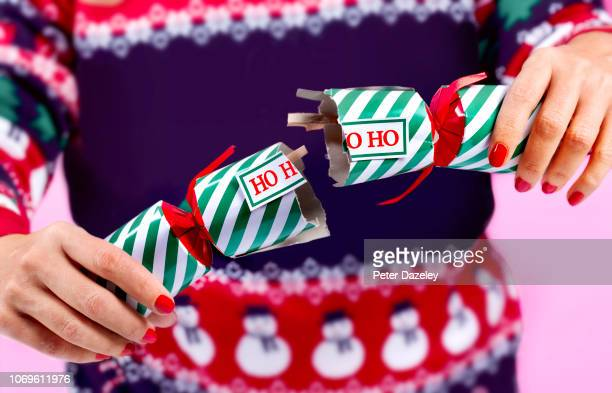 woman alone at christmas, pulling a cracker with herself - solitude stock pictures, royalty-free photos & images