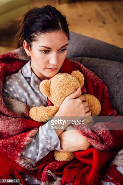 woman alone holding a teddy close - postpartum depression stock photos and pictures
