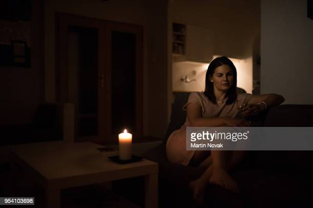 woman alone in dark room having a drink - candle light stock pictures, royalty-free photos & images
