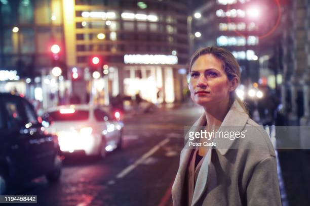 woman alone on city street at night - cream coloured blazer stock pictures, royalty-free photos & images