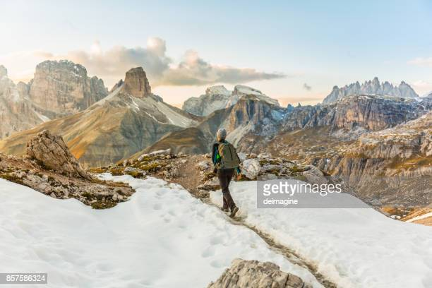woman alone trekking on the mountain path - dolomites stock pictures, royalty-free photos & images