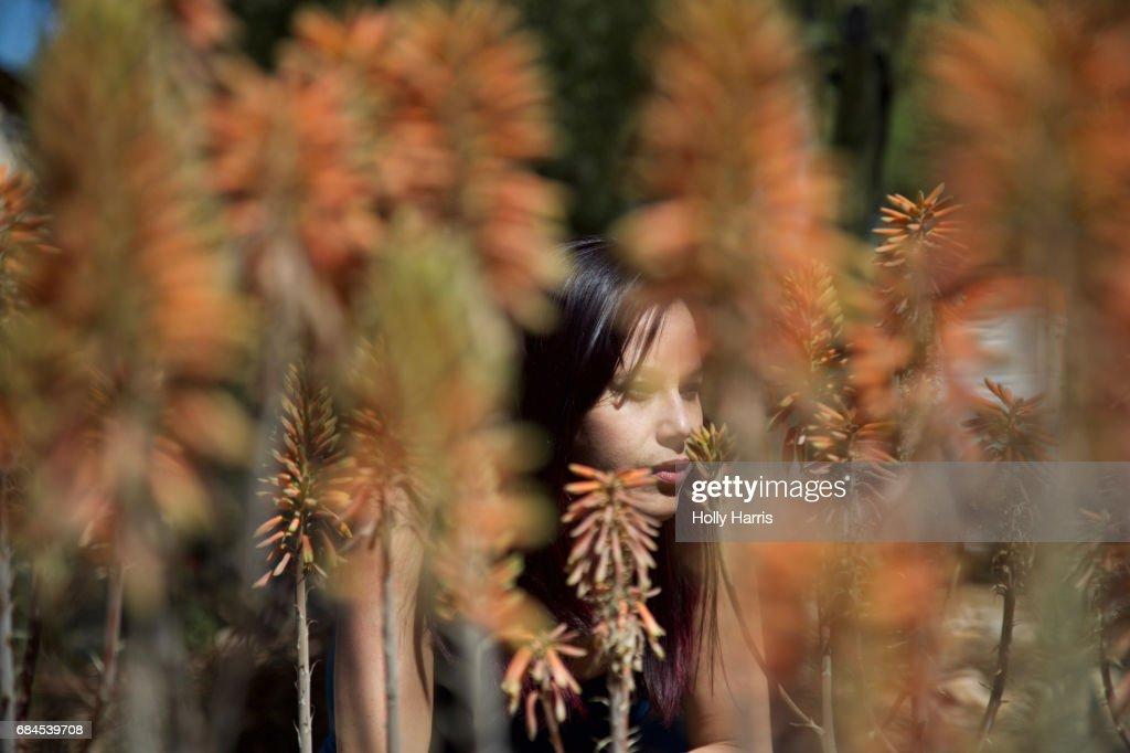Woman amidst orange plants in desert garden : Stock Photo