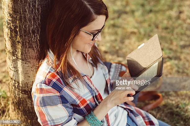 Woman among nature reading an e-book