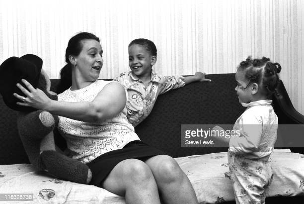 Woman amuses two children with a soft toy in London's East End, circa 1970.