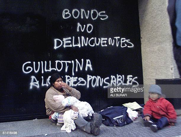 A woman an her children begg outside of Banco Rio in the financial district of Buenos Aires 18 June 2002 AFP PHOTO/Ali BURAFI Una mujer con sus dos...