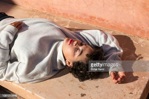 young woman laying in the sun - femme marocaine photos et images de collection