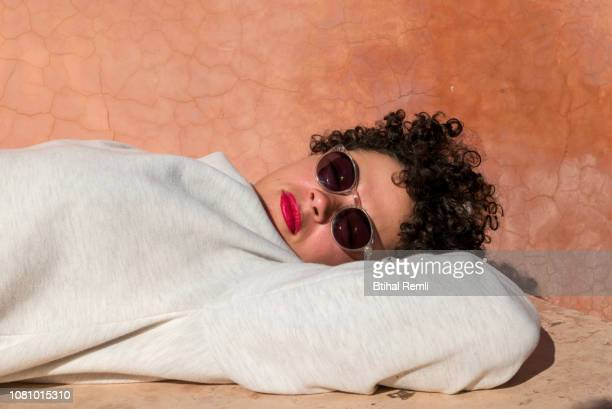 young woman laying in the sun - red lipstick stock pictures, royalty-free photos & images