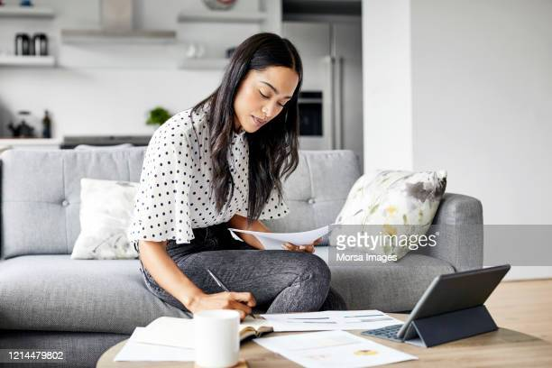 woman analyzing documents while sitting at home - saving stock pictures, royalty-free photos & images